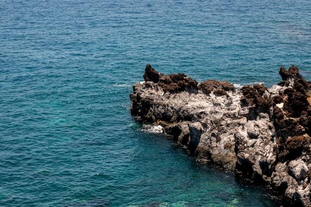 Água do mar azul lindo com pedras