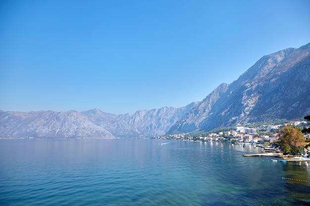 Água do mar e montanhas em um dia ensolarado com céu azul na baía de boka kotor, montenegro