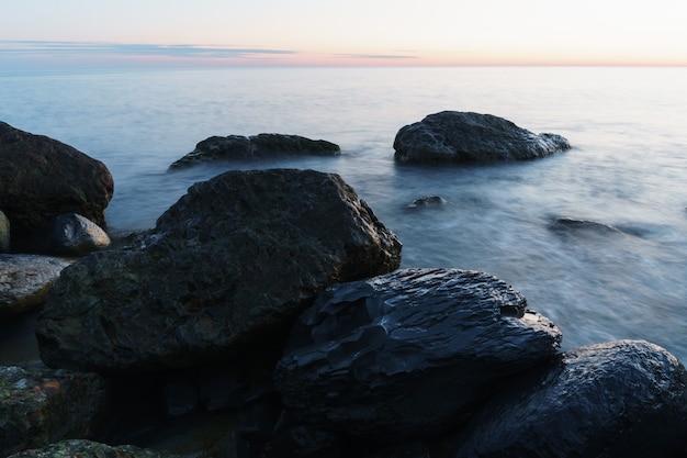 Água do mar lavando as rochas da costa. uma foto de longa exposição do mar