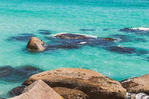 Água do oceano turquesa e as rochas, imagem de fundo natural