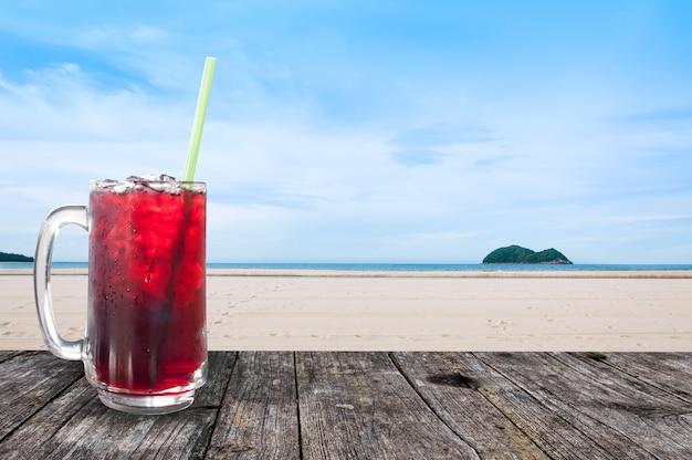 Água doce de suco fresco de roselle e gelo em um copo de café gelado na mesa de madeira com paisagem de praia, vista de fundo da natureza, bebidas saudáveis de verão com gelo