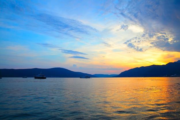 Água e céu coloridos ao pôr do sol na baía de kotor, montenegro