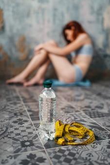 Água e fita métrica contra mulher anoréxica doente, perda de peso, anorexia. conceito de queima de gordura ou calorias, doença médica, nervosa