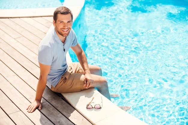 Água é ótima! vista superior de um jovem alegre em uma camisa pólo sentado à beira da piscina e sorrindo