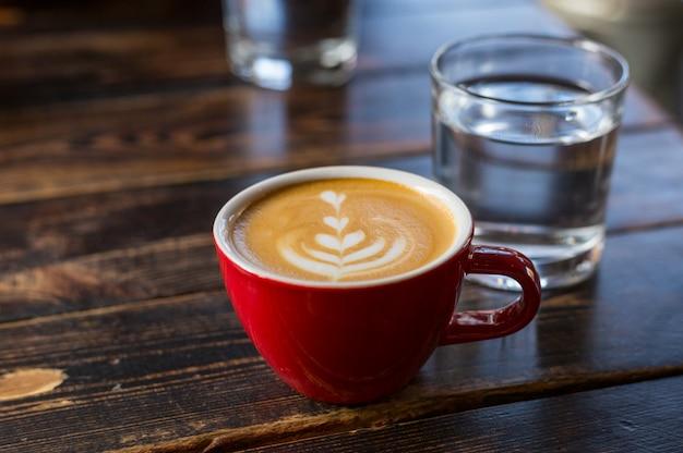 Água e xícara de café vermelha com latte art na mesa de madeira. mesa no café. conceito de café da manhã fácil. copo e copo pequeno de cerâmica