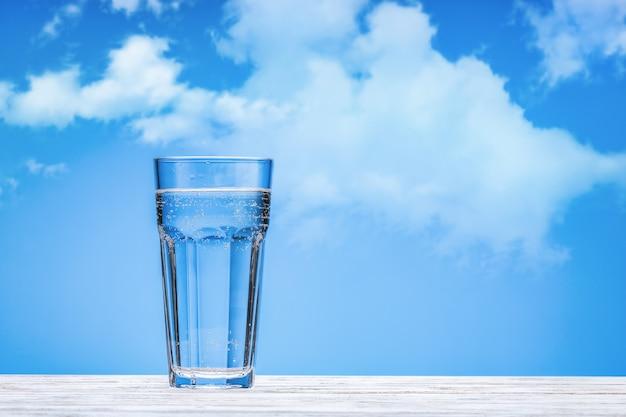 Água em um copo grande de vidro na superfície de madeira branca. fundo azul com nuvens, copie o espaço.