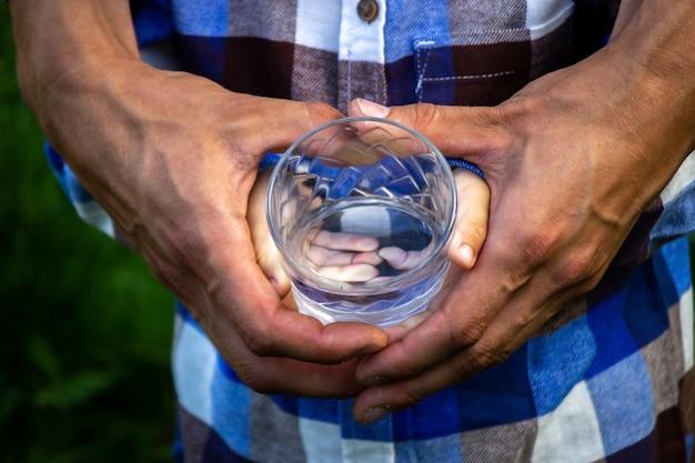 Água em um copo nas mãos de uma criança e de um pai. natureza. foco seletivo
