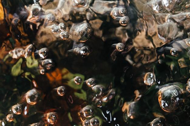 Água em um grande recipiente de metal uma imagem textural da agitação do líquido