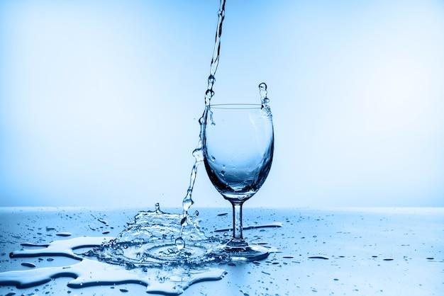 Água espirrando do vidro isolado na parede azul