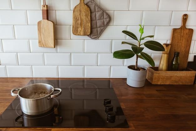 Água fervendo em uma panela e uma panela em um fogão de indução na cozinha branca moderna