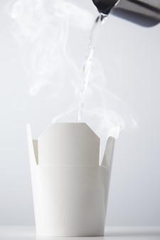 Água fervente sendo derramada de um bule de aço inoxidável para um recipiente de caixa de ramen de papelão branco isolado no branco