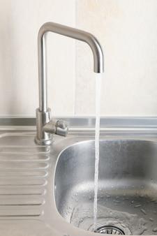 Água fluindo da torneira da pia da cozinha
