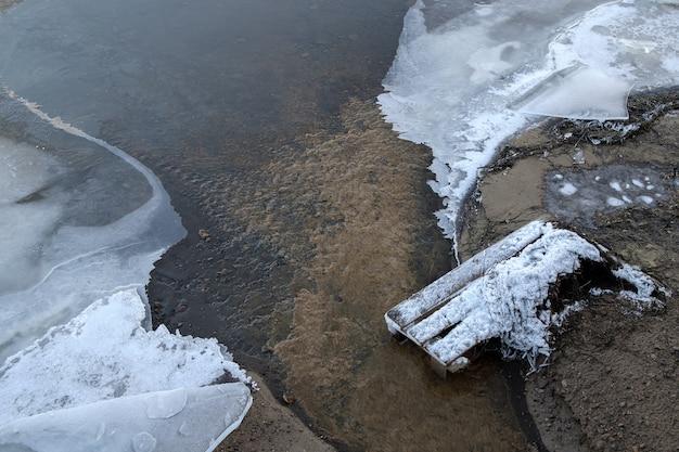 Água fluindo entre blocos de gelo. a superfície de um rio congelado em um dia de inverno.