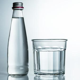 Água fresca e fria, pura em um copo com uma garrafa. água purificada em um copo sobre uma mesa cinza. água na mesa cinza.