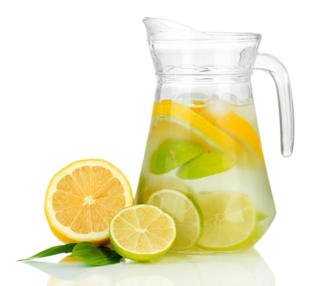 Água fria com limão, limão e gelo na jarra isolada no branco