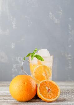 Água gelada com laranjas, hortelã da desintoxicação em um copo na parede de madeira e emplastro, vista lateral.