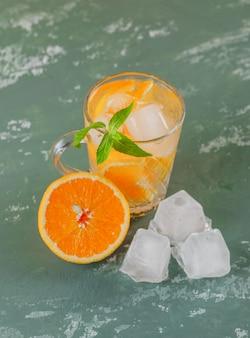 Água gelada de desintoxicação com laranja, hortelã em um copo de gesso, vista de alto ângulo.