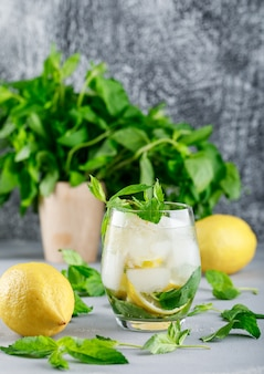 Água gelada de desintoxicação com limões e hortelã em um copo na superfície cinza e grunge