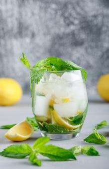 Água gelada de desintoxicação com limões e hortelã em um copo na superfície grunge e cinza