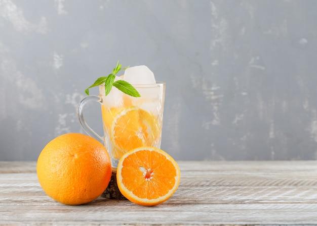 Água gelada de desintoxicação em um copo com laranjas, vista lateral de hortelã no fundo de madeira e gesso