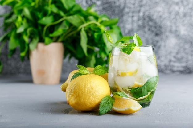 Água gelada de desintoxicação em um copo com limões e hortelã vista lateral na superfície cinza e grunge