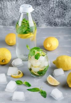 Água gelada de desintoxicação em vidro e garrafa com limões, hortelã vista de alto ângulo na superfície cinza e suja