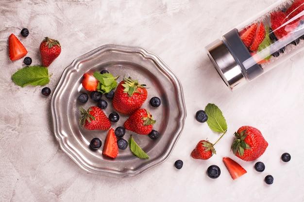 Água infundida em garrafa de vidro e frutas frescas