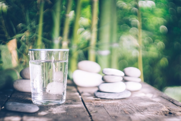 Água limpa derramando no copo ao lado das pedras