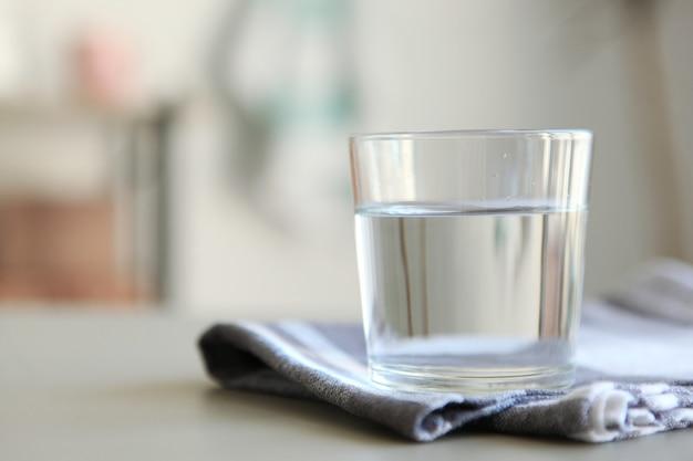 Água limpa em um copo e garrafa na mesa