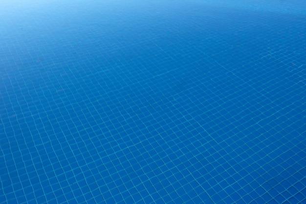 Água límpida e azul na piscina, por meio da luz do sol. fundo de água.
