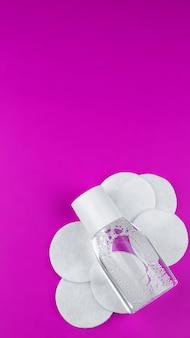 Água micelar em frasco transparente com algodão. fotografado de cima contra um fundo rosa.