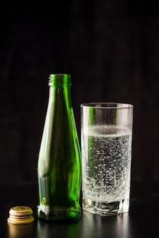 Água mineral em copo alto. parede escura com uma garrafa e um copo de água.