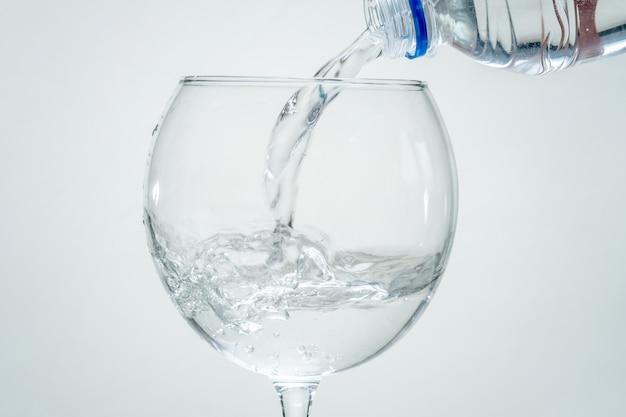 Água mineral pura e saudável é despejada de uma garrafa em um vidro transparente sobre um fundo branco