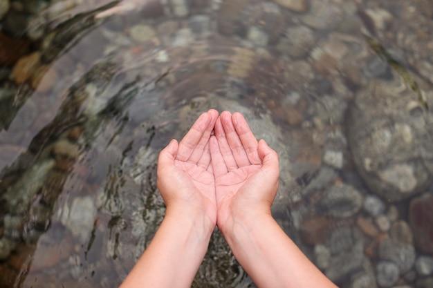 Água natural transparente nas mãos das mulheres