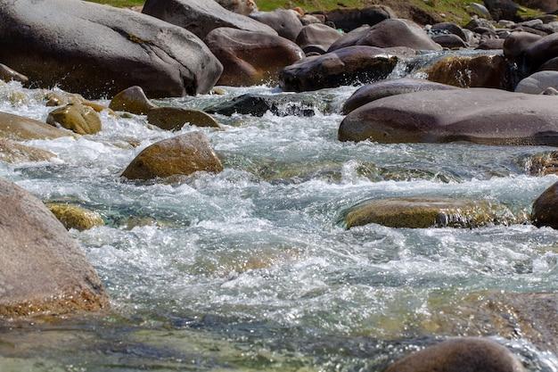 Água no rio raging da montanha. fundo natural bonito de pedras e água. textura de água limpa e rio rápido. plano de fundo para inserir texto. turismo e viagens.