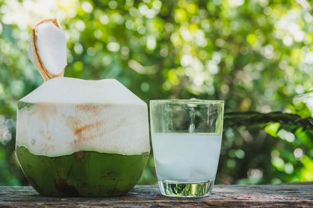 Água orgânica fresca do coco no vidro na tabela de madeira.