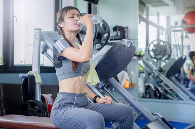 Água potável apta da mulher de uma garrafa após o exercício no gym da aptidão.