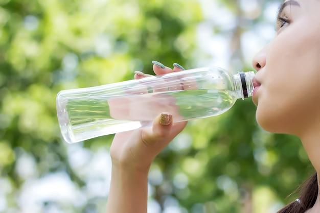 Água potável asiática da mulher nova após o exercício do exercício.