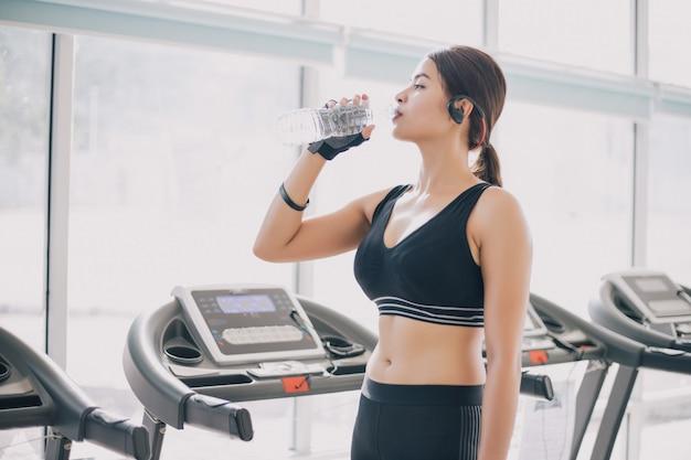 Água potável asiática de ásia da mulher após exercícios no gym.
