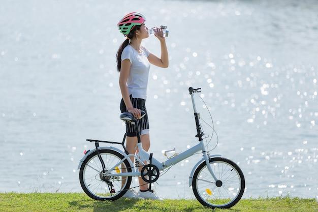 Água potável da mulher após a bicicleta de exercício.