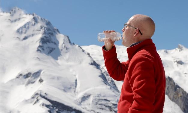 Água potável de alpinista na montanha