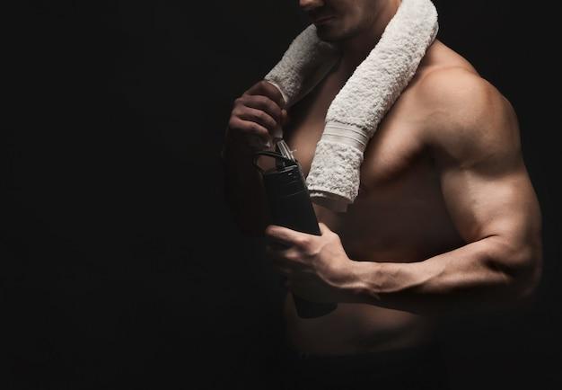 Água potável de fisiculturista masculino após treino com uma toalha no pescoço