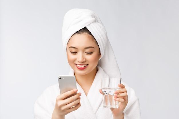 Água potável de mulher bonita jovem saudável, maquiagem natural de rosto de beleza com segurando o telefone móvel, isolado sobre