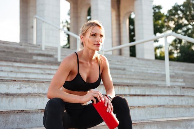 Água potável de mulher jovem forte bonita esportes