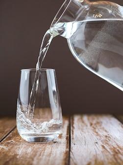 Água potável despejando do jarro no copo