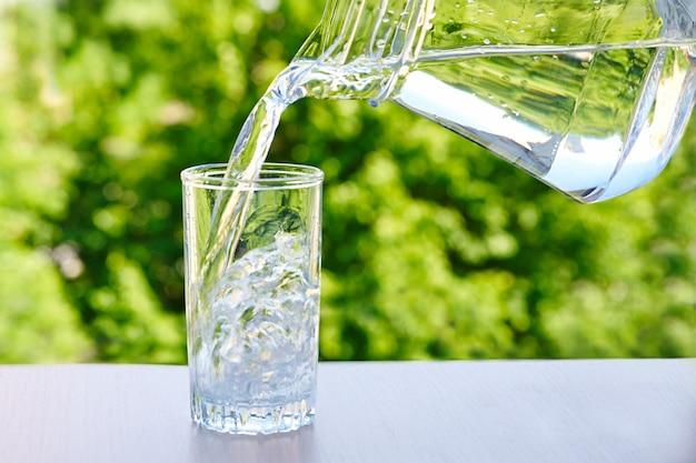 Água potável é despejada de uma jarra em um copo sobre uma mesa de madeira