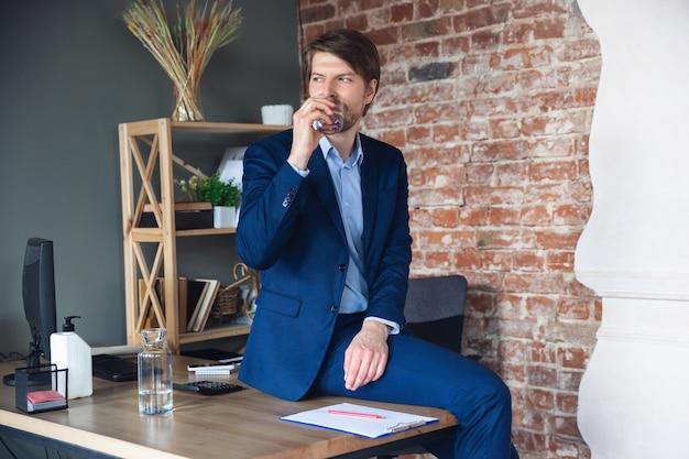 Água potável em cima da mesa. jovem, gerente, volta ao trabalho em seu escritório após a quarentena, sente-se feliz e inspirado. voltando à vida normal. negócios, finanças, conceito de emoções.