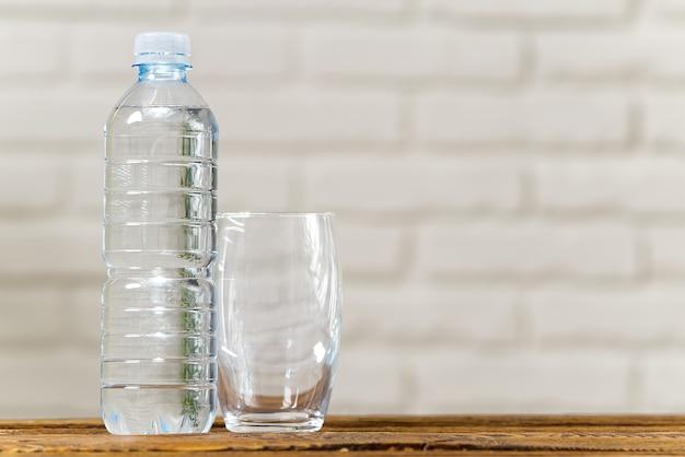 Água potável em garrafa de plástico na mesa de madeira e espaço de cópia de conceito de saúde de parede branca