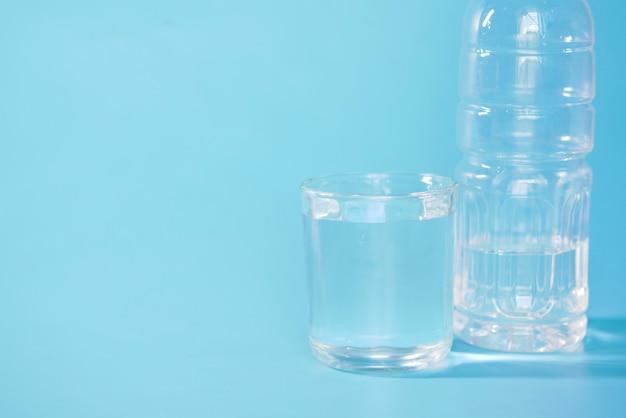 Água potável fresca em uma garrafa de plástico e um copo de água no azul