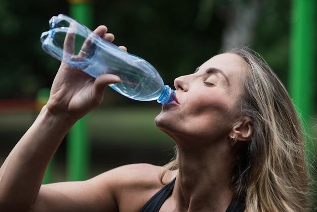 Água potável muscular atlética da menina após o treinamento. o conceito de um estilo de vida saudável